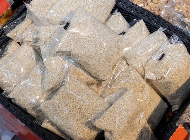 Naturalne nasiona sezamu pakowane w woreczki foliowe i sprzedawane w sklepie. nasiona sezamu są już na półce i gotowe do sprzedaży na rynku. dieta, zdrowe odżywianie.