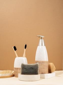 Naturalne, organiczne produkty do pielęgnacji. ręcznie robione mydło, drewniana szczotka i bambusowe szczoteczki do zębów. kreatywna kompozycja akcesoriów spa na beżowym tle