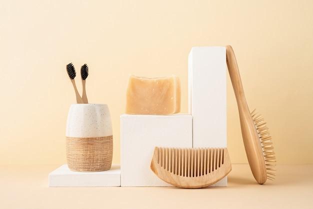 Naturalne, organiczne produkty do pielęgnacji. ręcznie robione mydło, drewniana szczotka i bambusowe szczoteczki do zębów na białych podium. kreatywna kompozycja akcesoriów spa na beżowym tle