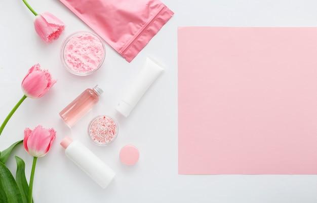 Naturalne organiczne produkty kosmetyczne z różowymi kwiatami na białym tle z pustą pustą kartą