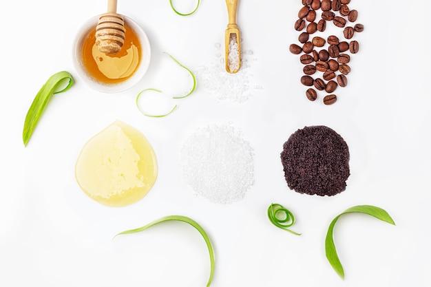 Naturalne organiczne składniki domowej roboty do pielęgnacji skóry. kosmetyk oczyszczająco-odżywczy. produkty kosmetyczne: krem, miód, peeling kawowy, wśród zielonych liści na białym tle. zamknij się, skopiuj miejsce na tekst