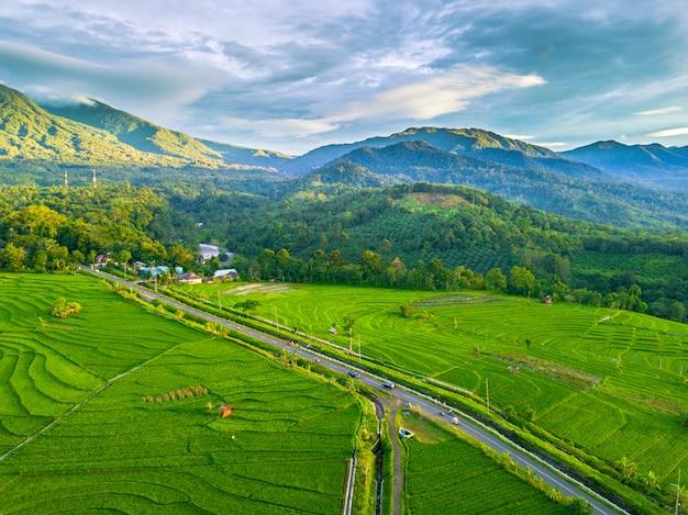 Naturalne piękno gór, pól i nieba. zielony indonezyjski naturalny krajobraz w rejonie bengkulu ze zdjęciami lotniczymi