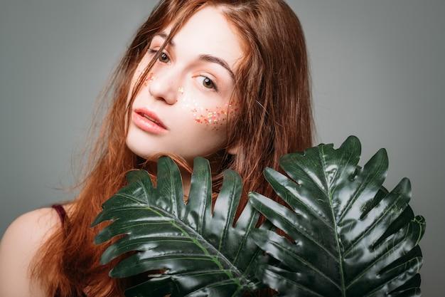 Naturalne piękno kobiety. organiczna pielęgnacja skóry. leczenie uzdrowiskowe. młoda kobieta z liśćmi monstera.