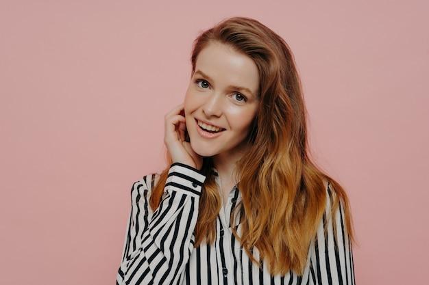 Naturalne piękno. urocza nieśmiała nastolatka ubrana w koszulę trzymająca rękę w pobliżu twarzy i uśmiechnięta zalotnie do kamery, stojąc na białym tle na różowym tle, piękna kobieta pozuje w studio