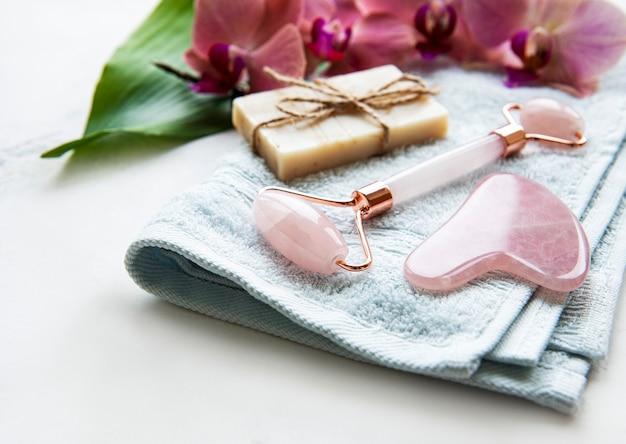 Naturalne produkty do pielęgnacji skóry i spa z ręcznie robionym naturalnym mydłem, jadeitowym wałkiem do twarzy i bawełnianym ręcznikiem zbliżenie, koncepcja spa i pielęgnacji skóry, naturalne organiczne produkty wellness, home-spa