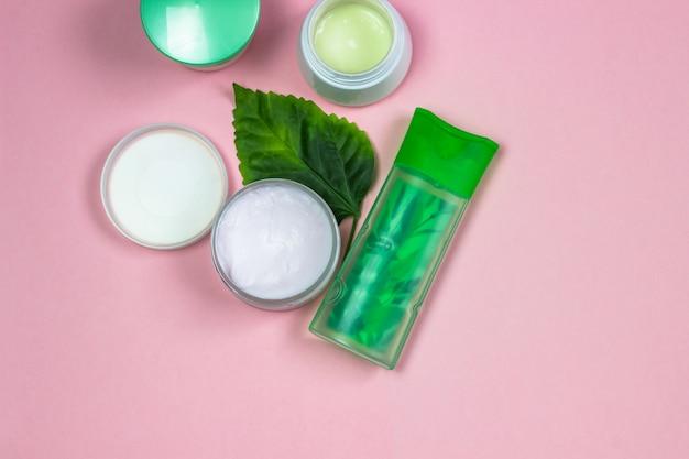 Naturalne produkty kosmetyczne na różowym tle. słoiki, butelki z kremem naturalnym
