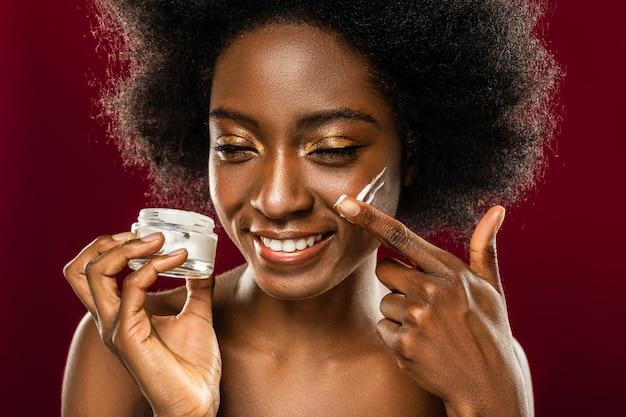 Naturalne składniki. zachwycona miła kobieta uśmiechnięta podczas korzystania z organicznych kosmetyków do twarzy