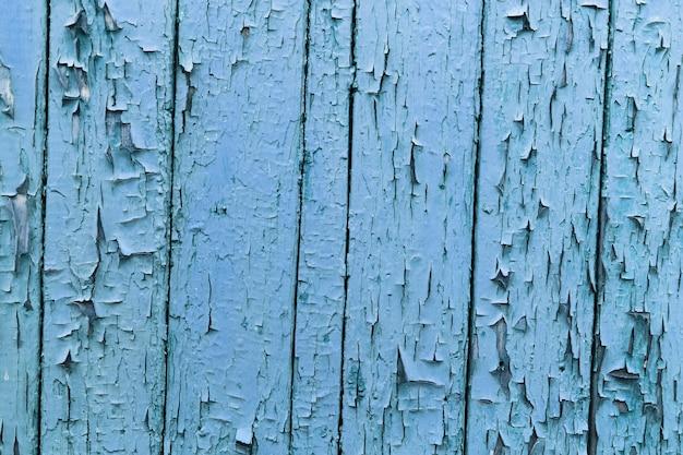 Naturalne streszczenie tło teksturowanej pękniętej drewnianej ścianie w kolorze niebieskim.