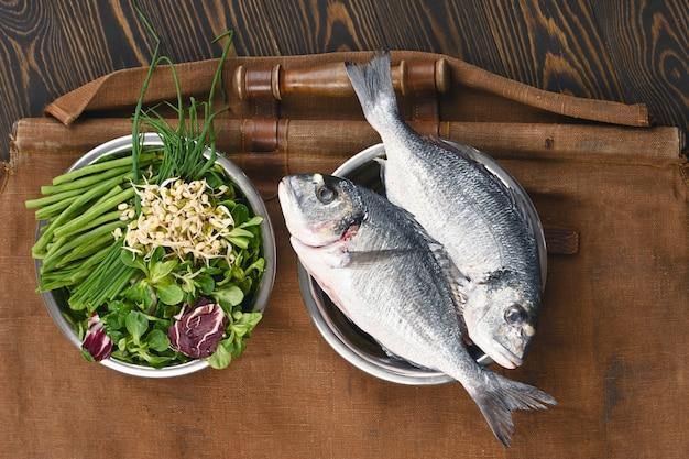 Naturalne surowe składniki zdrowych składników karmy dla zwierząt domowych w poszczególnych miseczkach na brązowym drewnianym.
