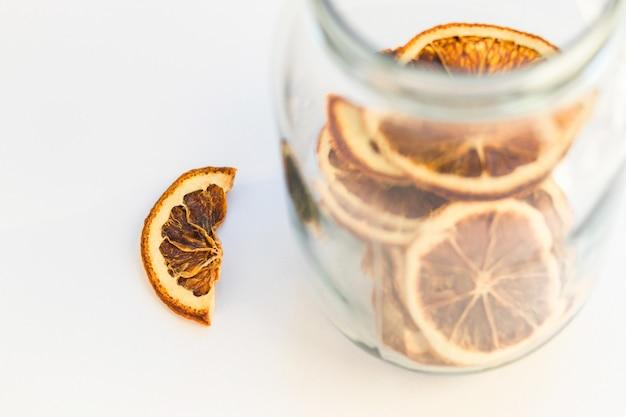 Naturalne suszone plastry pomarańczy w szklanym słoju. zdrowa przekąska. dekoracje świąteczne i noworoczne. widok z góry.