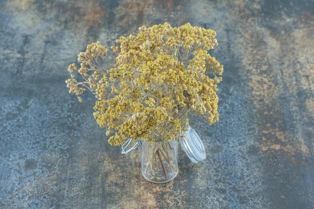 Naturalne suszone żółte kwiaty w szklanym słoju.