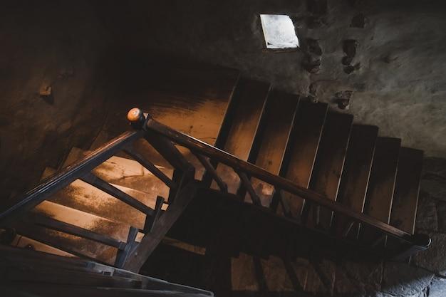 Naturalne światło oświetlone starymi drewnianymi schodami z poręczą w ciemności.