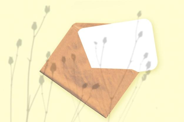 Naturalne światło rzuca cień z rośliny na kopertę z kartką białego papieru leżącą na żółtym tle z teksturą. makieta