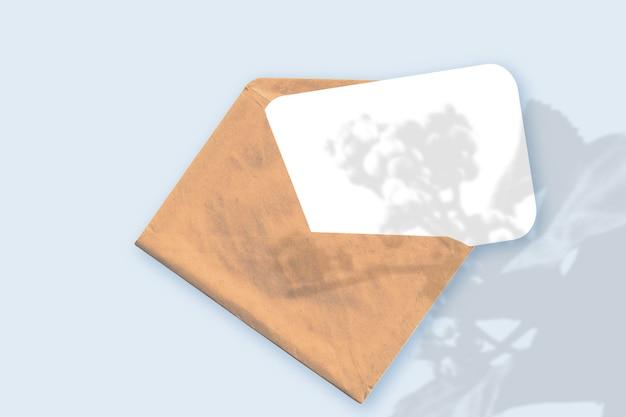 Naturalne światło rzuca cienie z rośliny na kopertę z kartką białego papieru leżącą na niebieskim tle z teksturą