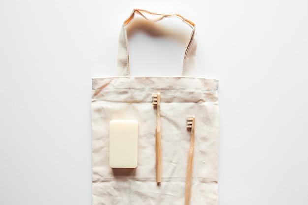 Naturalne szczotki wykonane z drewna i mydła na tle betonu, bambusowe szczoteczki do zębów i szczoteczka do ciała, ręcznie robione mydło z luffą