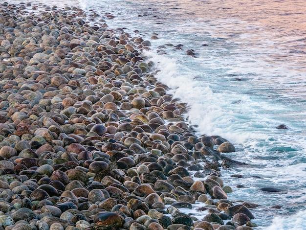 Naturalne tło kamyków nad brzegiem morza