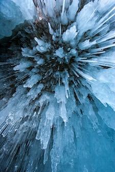 Naturalne tło tekstury. ostre niebieskie sople zwisające z sufitu jaskini. widok z dołu. orientacja pionowa.
