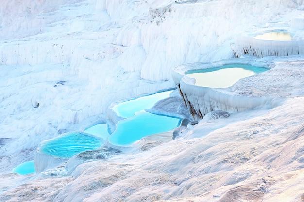 Naturalne trawertynowe tarasy pamukkale wypełnione niebieską wodą