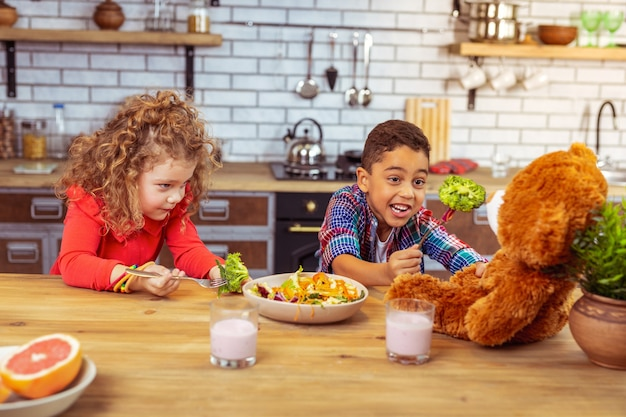 Naturalne witaminy. zachwycony chłopiec trzymający uśmiech na twarzy i trzymający brokuły na widelcu