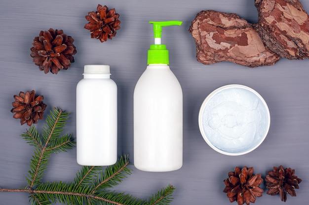 Naturalni kosmetyki na szarym tle z jodeł gałąź i rożkami, kopii przestrzeń. pielęgnacja ciała i twarzy.