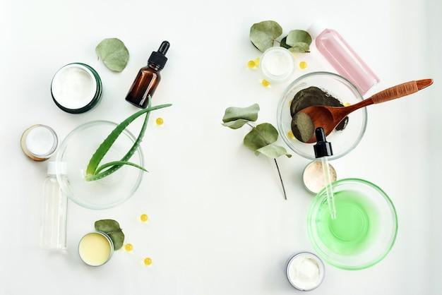 Naturalni kosmetyki z liśćmi aloesu i olejem do domowej roboty spa biały stół tło makiety. kosmetyki dla twarzy z płukanką od ziele na białym tło odgórnego widoku copyspace