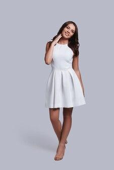 Naturalnie piękna. pełna długość atrakcyjnej młodej kobiety w białej sukni patrzącej na kamerę i uśmiechającej się stojąc na szarym tle