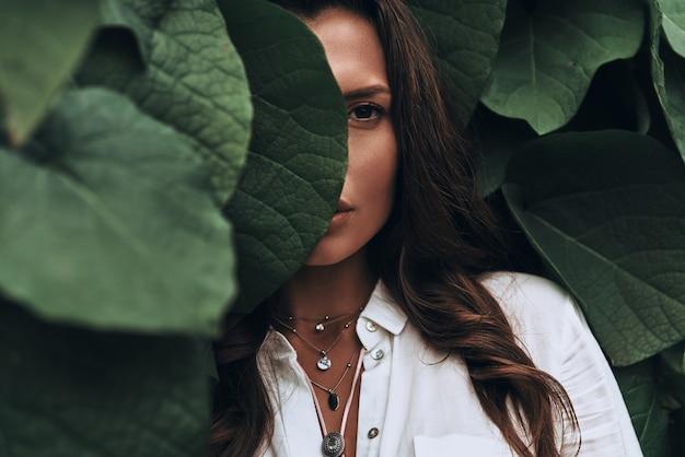 Naturalnie piękna. zbliżenie młodej kobiety patrzącej na kamerę stojącą wśród liści na zewnątrz
