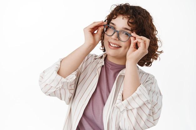 Naturalnie uśmiechnięta dziewczyna z kręconymi włosami, założyła okulary i wygląda na szczęśliwą, przymierza nowe okulary w sklepie optycznym, stoi w codziennych ubraniach na białym tle.