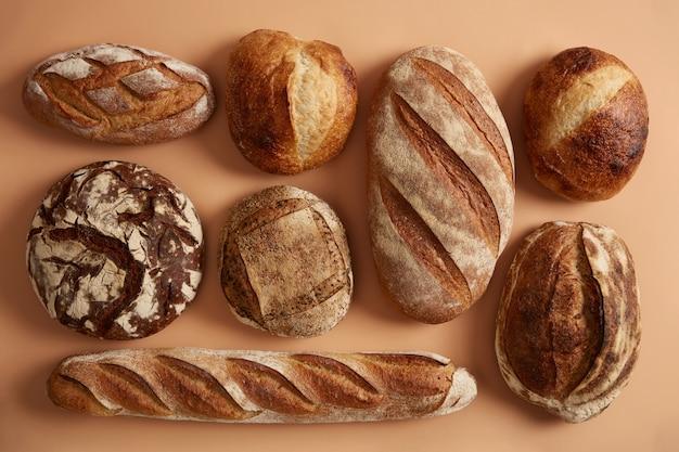 Naturalny chleb na zakwasie wypiekany z organicznej mąki. pszenica orkisz, kasza gryczana, chleb żytni na białym tle na beżowym tle. koncepcja piekarni i rolnictwa. pożywne świeżo upieczone produkty lekkostrawne