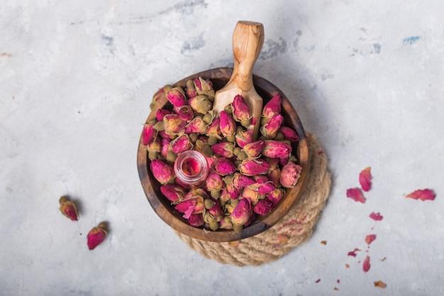 Naturalny czysty olej różany lub woda perfumowana w butelkach do spa, pielęgnacji skóry lub aromaterapii z różowymi suchymi różami. koncepcja kosmetyków organicznych. selektywne ustawianie ostrości