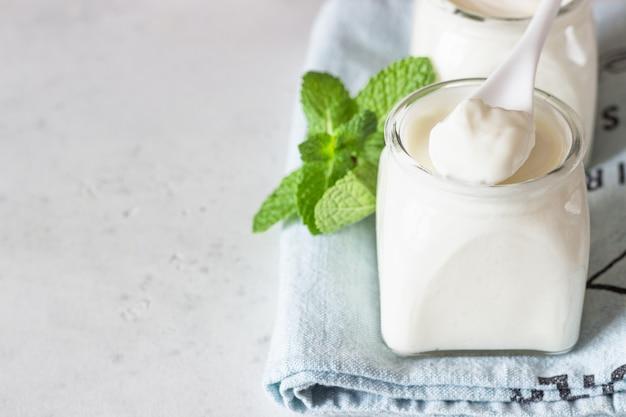 Naturalny domowy jogurt organiczny w szklanych słoikach świeży i naturalny fermentowany produkt mleczny