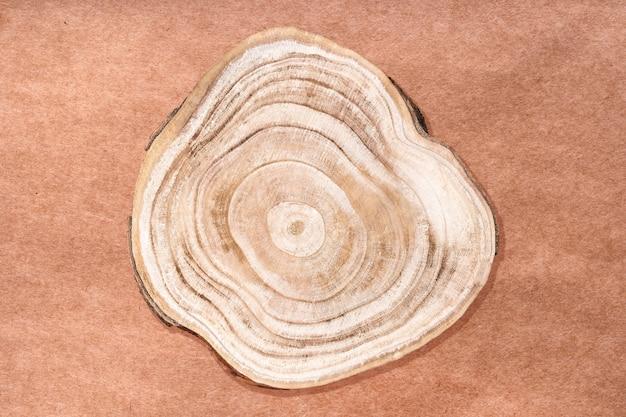 Naturalny ekologiczny cokół ekologiczny. drewniany przekrój poprzeczny wycięty na powierzchni papieru rzemieślniczego eco, ujęcie studyjne. prezentacja nagród dla produktów kosmetycznych. makieta reklamy produktu.