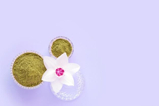 Naturalny henna w proszku i biały kwiat w kobiecej dłoni na różowym tle. pojęcie kobiecego piękna i kosmetologii. farbowanie brwi i włosów.