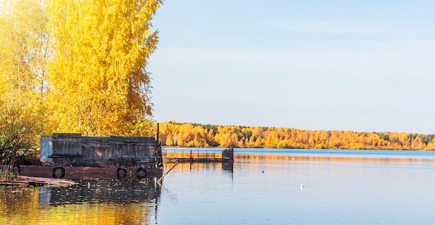 Naturalny jesienny krajobraz. odbicie żółto-pomarańczowych liści w wodzie, jeziorze lub stawie.