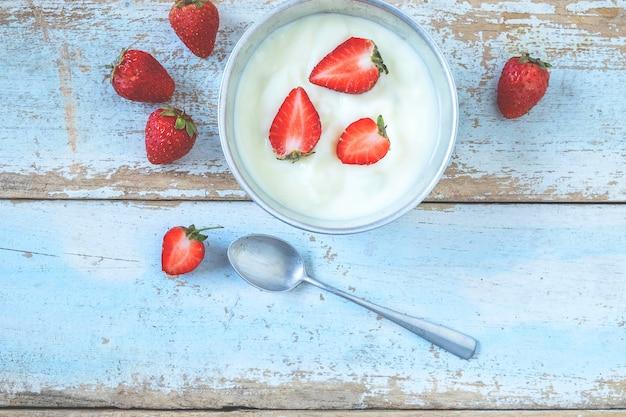 Naturalny jogurt i truskawkowa owoc na drewnianym tle