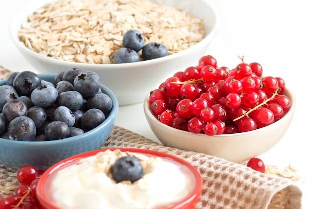 Naturalny jogurt, świeże jagody i płatki na serwetce. koncepcja zdrowego śniadania