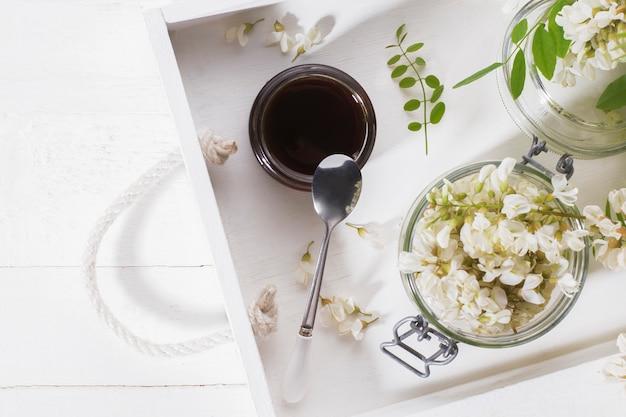 Naturalny miód akacjowy w słoiku na białej tacy. widok z góry
