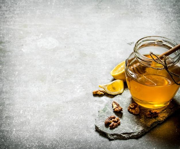 Naturalny miód w słoiku, cytryna i orzechy włoskie na kamiennym tle