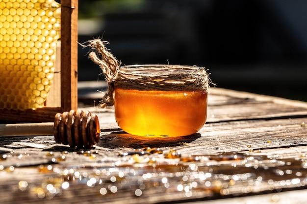 Naturalny miód z łyżką na starym rustykalnym stole