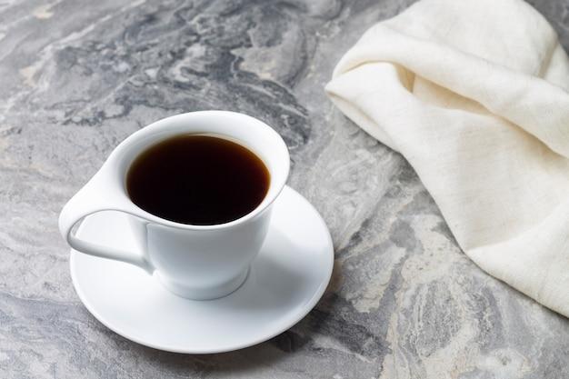 Naturalny napój z cykorii w białej filiżance ze spodkiem na marmurowym tle.