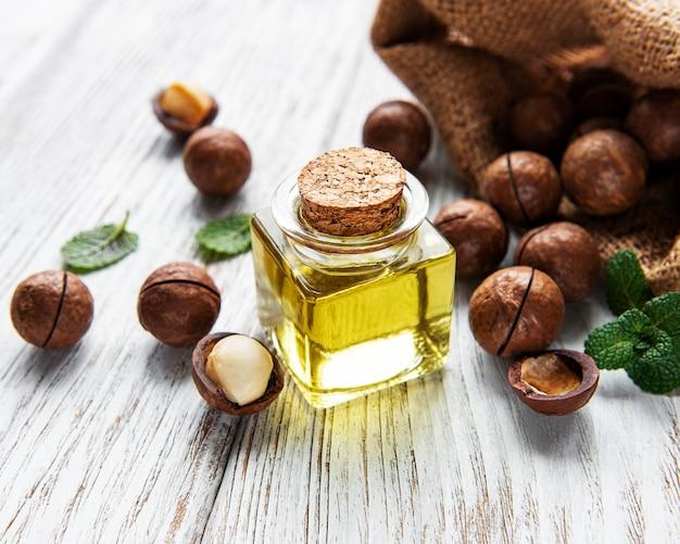 Naturalny olej makadamia i orzechy makadamia na drewnianej desce