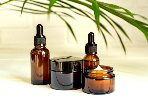 Naturalny olejek eteryczny, serum i krem w brązowych szklanych butelkach na drewnianym podium.