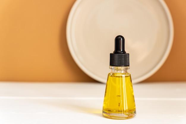 Naturalny olejek eteryczny, szklana butelka na serum na drewnianym podium.