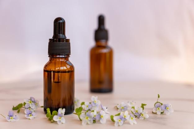 Naturalny olejek eteryczny, szklana butelka na serum na szarej powierzchni