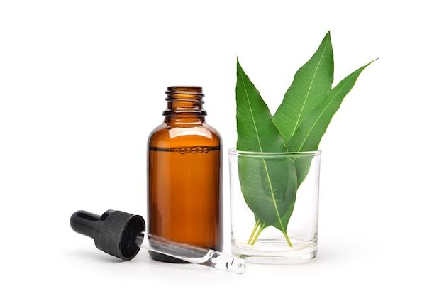 Naturalny olejek eukaliptusowy w bursztynowej butelce z zakraplaczem z zielonymi liśćmi na białym tle.