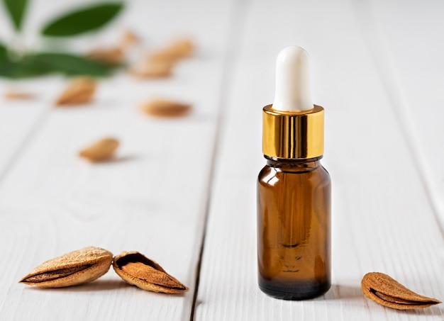 Naturalny olejek migdałowy z migdałami i zielonymi liśćmi