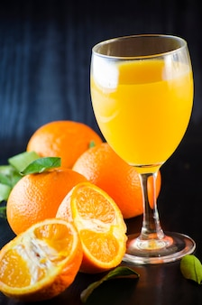Naturalny organiczny świeży sok mandarynki w szklance na ciemnym tle