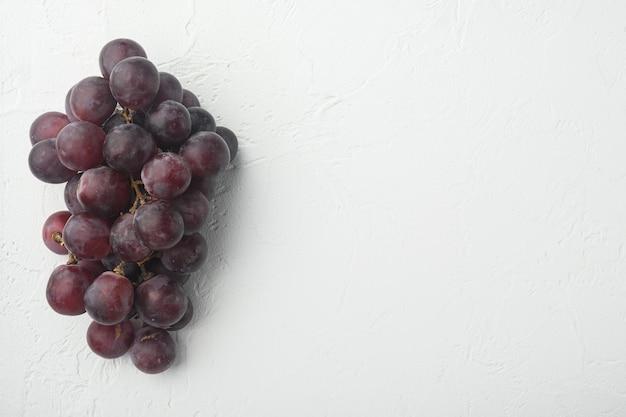 Naturalny organiczny zestaw soczystych winogron, ciemnoczerwone owoce, na białym tle kamienia, widok z góry płasko leżący, z miejscem na kopię na tekst