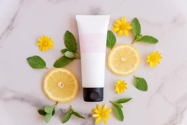 Naturalny produkt do pielęgnacji skóry z witaminą c z plastrami świeżych soczystych owoców cytryny na marmurowej powierzchni