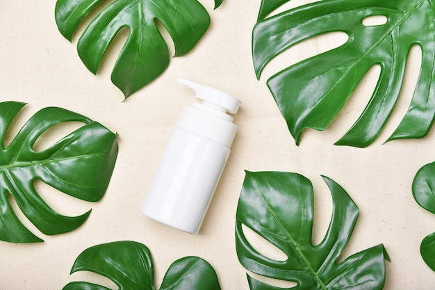 Naturalny produkt kosmetyczny do pielęgnacji skóry, pojemniki na butelki kosmetyczne z zielonymi liśćmi natury, pusta etykieta dla makiety marki ekologicznej spa, ziołowa zdrowa pielęgnacja skóry.